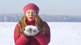 Young woman in pink clothes blowing on snow. In a winter field stock video