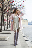 Young woman in pink coat walks on the Red Square in Moscow Stock Image