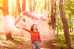 Young woman with pink color smoke bomb Stock Images