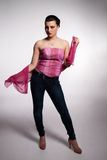 Young woman in pink corset, jeans, high heels with pink scarf Stock Photography