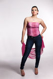 Young woman in pink corset, jeans, high heels with pink scarf Royalty Free Stock Photo