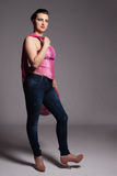 Young woman in pink corset, jeans, high heels with pink scarf Stock Images