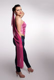 Young woman in pink corset, jeans, high heels with pink scarf Stock Image