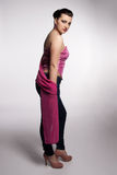 Young woman in pink corset, jeans, high heels with pink scarf Stock Photo