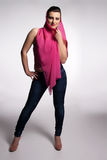 Young woman in pink corset, jeans, high heels with pink scarf Royalty Free Stock Image