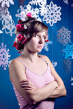 Young woman in pink curlers and pink dress is standing with crossed arms and looking at camera displeased with paper snowflakes Royalty Free Stock Photography