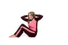 Young woman in pink doing situps or crunches. Young, pretty woman in pink doing crunches or sit-ups Royalty Free Stock Image