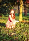 Young woman in pink dress crouching in the park, during evening stock photo