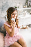 Young woman in pink dress holding cookies Royalty Free Stock Image