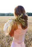 Young woman in pink dress holding wheat ears and hat in her hands Stock Photos