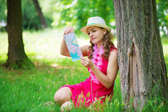 Young woman in pink dress with map at green summer park Stock Photos