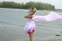 Young woman with pink fabric fluttering in the win Royalty Free Stock Photo