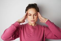 Young woman in pink hoody with a severe headache with the hands in the head over white empty wall on background. Beauty. And healthcare concept Stock Photos