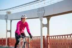 Young Woman in Pink Jacket Riding Road Bicycle on the Bridge Bike Line in the Cold Sunny Autumn Day. Healthy Lifestyle. Young Woman in Bright Pink Jacket Riding royalty free stock photo