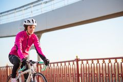 Young Woman in Pink Jacket Riding Road Bicycle on the Bridge Bike Line in the Cold Sunny Autumn Day. Healthy Lifestyle. Young Woman in Bright Pink Jacket Riding stock image