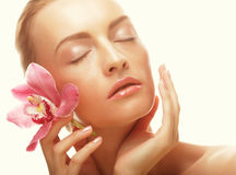 Young woman with pink orchid Royalty Free Stock Photo