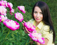 Young woman with pink peonies Stock Photography