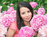 Young woman with pink peonies Stock Images