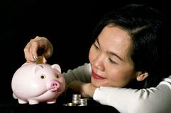 Young woman with pink piggy bank Royalty Free Stock Image