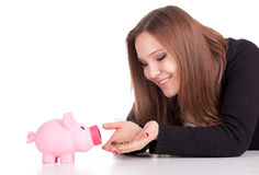Young woman with pink piggy bank Royalty Free Stock Photography