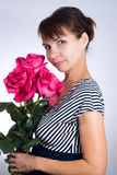 Young woman with pink roses. Portrait of young beautiful woman with three gorgeous pink roses on gray background Royalty Free Stock Photos