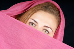 Young woman with pink scarf. Portrait of a beautiful young woman peeking over a pink scarf Stock Image