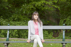 Young woman in pink seated on a bench Stock Photos