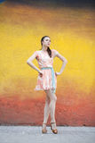Young woman in pink sexy dress. Against color wall Royalty Free Stock Images