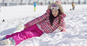 Young woman in pink snowsuit with ski goggles Stock Photo