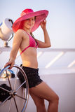 Young woman in pink sunhat on cruise ship deck looking at camera Royalty Free Stock Photos