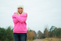 Young woman in a pink sweater and white hat Stock Photography