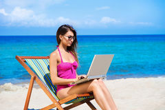 A young woman in a pink swimsuit with a computer on the beach Royalty Free Stock Photos