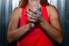 Young woman in pink top greases hands with magnesia. Close-up Young woman in pink top greases hands with magnesia before training against a gray wall background royalty free stock image