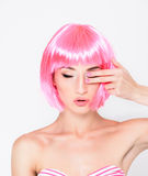 Young woman in pink wig posing on white background Royalty Free Stock Photos