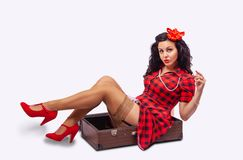 Young Woman Pinup Style Sitting In A Suitcase Stock Photo