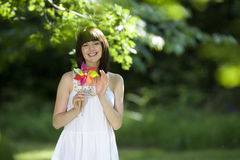 Young woman with pinwheel outdoors, smiling, portrait Stock Images