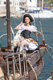 Young woman in pirate costume is posing. Girl in pirates costume posing on the deck of boat Stock Photos