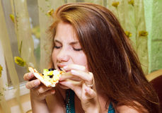 Young woman with pizza atrestaurant Stock Image
