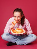 Young woman with pizza sitting on the floor Stock Photo