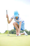 Young woman placing ball while kneeling at golf course Stock Image