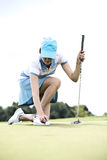 Young woman placing ball while kneeling at golf course Stock Photography