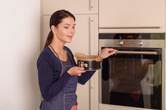 Young woman placing a cake in the oven Royalty Free Stock Photo
