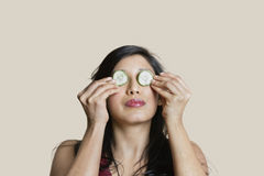 Young woman placing cucumber on eyes over colored background Royalty Free Stock Photos
