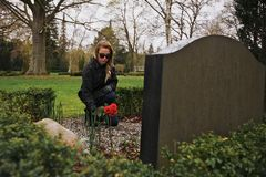 Young woman placing roses at a cemetery Royalty Free Stock Image