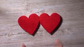 Young woman placing two red hearts on a wooden table, top view. Romance, love, Valentine's day, relationship concepts stock video