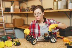 Beautiful caucasian young woman working in carpentry workshop at table place royalty free stock photos