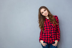 Young woman in plaid shirt posing on gray background Stock Photo