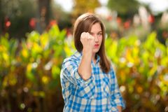 Young woman in a plaid shirt posing in park stock images
