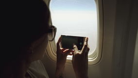 Young woman in plane taking photo on her smartphone during flight. In airplane cabin stock video footage