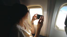 Young woman in plane taking photo on her smartphone during flight. In airplane cabin stock video